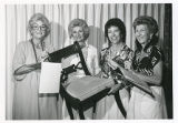 Vi Friedland, Judith Miller, Marjorie Platt, and others holding chair at auction, University Women